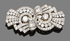 A diamond double-clip brooch, circa 1935.  Each opposing scroll of openwork design set throughout with old brilliant, single and baguette-cut diamonds, diamonds approx. 3.40ct total, length 5.6cm