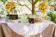 The vibrant bouquets of yellow flowers with lemons in the vases add a beautiful summer feel to this table display. Wedding coordination by Amazae Special Events.