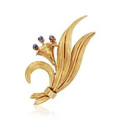 C. 1960. Our Estate collection presents this nature-inspired pin from Tiffany Jewelry. The floral motif blossoms in 18kt yellow gold with .10 ct. t.w. sapphire anthers. With that desirable vintage look, it's sure to add a charming element to your wardrobe. Revolver safety, blue sapphire Tiffany Jewelry floral pin. <b>Exclusive, one-of-a-kind Estate Jewelry.</b> Free shipping & easy 30-day returns. Fabulous jewelry. Great prices. Since 1952.