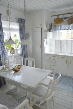 White kitchen with blue and white, checkered curtains.   My mom would love this kitchen!