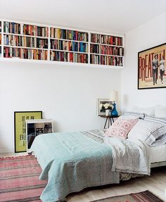 This creative bookshelf decorating idea -- placing three shelves near the ceiling -- is a great solution for a small bedroom space. It frees up the ground so both sides of the bed are easily accessible, and so that there's plenty of room for a bedside table.