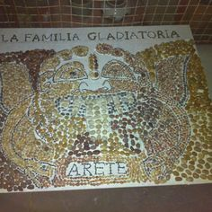 Gorgon, Day 11  The letters are done and I think they are legible.  I filled in some of the areas between the wings and the head on each side.  Once I get the larger pebbles even on each side, I can start using smaller pebbles to frame the words at the top, and then in between the letters.    The goal is to have this grouted a week from today so it will have time to cure before sealing and then put it in a van to go across country in 12 days.  I can do that!