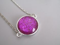 This simple but pretty pendant is handmade with a round silver-plated bezel tray, and a beautiful glass cabochon with a gorgeous fuchsia color on the bottom.