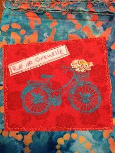 Painted bike on rose fabric with some French Knots spilling out of the basket.