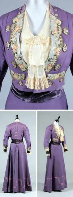 Lilac wool day ensemble, Maison H. Barry and Gobillot, ca. 1911. Short jacket with 18th century-style chain-stitched embroidery on blue silk collar & cuffs and small embroidered rosettes. Matching skirt with taffeta bands and buttons at hem, a blouse with velvet cuffs, and matching velvet cummerbund. Kerry Taylor Auctions