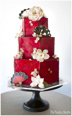 Cake Design by The Pastry Studio, Custom Cake features a rich red fondant base, sugar-paste florals, fans & piping touched with edible gold.