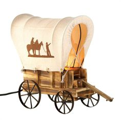 Western Wagon Table Lamp   Follow the wagon trail to discover the most charming lamp on the prairie. This tabletop wooden wagon lamp features metal wheels and a wagon cover with silhouettes of cowboys and horses. Uses 7W energy-efficient light bulb.  @ amazingwebshopperonline.com