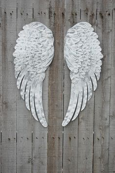 Romantic set of large hand painted metal angel wings. Done in white and accented in silver with a protective coating. They each have 3 sawtooth hangers on the back and can be hung several different wa