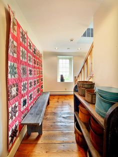Large quilt with bright pink sashing displayed on hallway wall