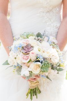 Crystal Springs Resort wedding photos in New Jersey, with photographer Mikkel Paige Photography. The couple's spring wedding had an outdoor ceremony with photos at this rustic, woodsy venue showing their blue and pink palette decor from getting ready to their reception. This detail picture shows the bride's succulent bouquet, with blue, peach and white flowers and roses, wrapped with raffia and burlap. Click through to see their complete wedding recap! #NewJerseywedding #MikkelPaige…