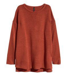 Широкий вязаный джемпер из мягкой пряжи. На джемпере спущенные плечи и длинные рукава, а также высокие разрезы по бокам. Спинка слегка удлиненная.