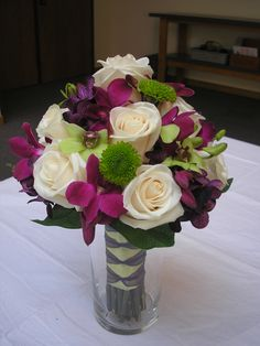 Bridesmaid bouquet of white roses, green button mums, jade and magenta dendrobium orchids.  wwwflowersofthefield.us