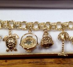 One of our custom creations! Fabulous charms bracelet with 14k yellow gold sea turtle, sweetgrass basket with lid, hand made southern belle by Glenn D. Wolfe, 3-D palmetto tree all on triple link charm bracelet | pricing varies  shop@goldcreationschas.com #charlestoncharmbracelet #customcreations