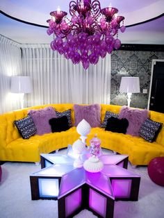 The fun Moroccan-style coffee table lights up making this living area the perfect party pad. The patent leather yellow sofa brings a punch of color to the space, and the circular cutout in the ceiling allows for the over-the-top purple crystal chandelier.