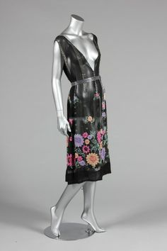 A beaded flapper dress, mid 1920s, of black chiffon adorned with a beaded flower garden to the hem and silver beaded arches, deep V-neckline front and back, with matching belt, bust approx 97cm, 38in (2)