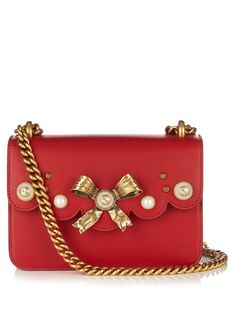 Gucci's ruby-red Peony bag reflects creative director Alessandro Michele's eccentric offering for Pre-AW16. It's crafted from lightly grained calf leather and elevated with an antiqued gold-tone metal bow, faux-pearls, and a gold-tone GG logo. The sliding chain shoulder strap makes it a versatile piece you can use daily.