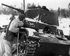 Swedish volunteer fighter inspecting a wrecked Soviet T-26 tank in Finland, 1940