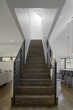 Modern home with Staircase. Stained oak flooring was used throughout the home's ground level, and continues up the main stairwell. Painted steel was used for the guardrails. Photo 6 of The Farmhouse Hardwood Stairs, Wood Staircase, Modern Staircase, Staircase Design, Stair Design, Staircase Remodel, Staircase Ideas, Staircase In Living Room, House Stairs