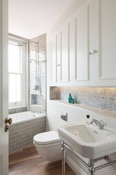 Built in white white cabinets adorning nickel knobs are situated above a blue mosaic tile shower niche located above a 2-leg washstand finished with a polished nickel vintage cross handle faucet.