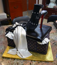 The bottom Louis Vuitton box is the actual cake and to add to the fashion style, an intricate Louboutine-inspired fondant shoe was added on top as well as a delicate scarf and rope detail.