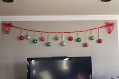 Christmas Wall Decoration ~ used a ribbon to make an ornament banner to hang across the top of the TV/fireplace and secured it with two thumbtacks. I like this simple, festive idea! Check out her other wonderful ideas. (Christmas Decorating on a Budget: Dec 2010)