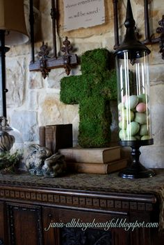 easter mantle with moss cross and apothecary jar with pastel eggs