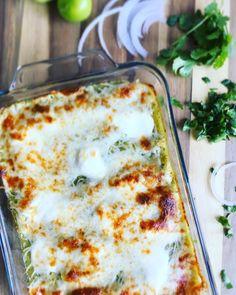 Tortillas de maíz rellenas de pollo cocido y desmenuzado, bañadas en salsa verde casera, cubiertas por crema y una generosa capa de queso blanco derretido, servidas con tiras de cebolla y un poco de cilantro picado.