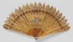 1825, England - Fan - Brisé minuet fan. Pierced horn sticks heavily ornamented with gilt; heads carved in alternating pagoda and Gothic shapes; painted scene with chinoiserie figures center; brown silk connecting ribbon. Mother-of-pearl rings on rivet.
