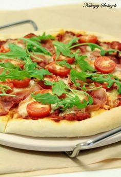 Domowa pizza z mozzarellą, szynką, pomidorkami i rukolą
