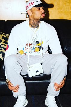 Chris Brown wearing Adidas Yeezy Boost 350 V2, Fan Merchandise Vintage T-Shirt, Fujifilm Instax Wide 300 Instant Film Camera, Yeezy Sply-350 Cap