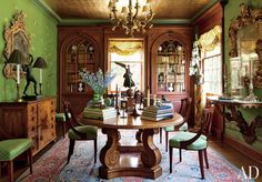 TRADITIONAL DINING ROOM BY TIMOTHY CORRIGAN INC.  A ceiling clad in gold leaf adds glamour to the dining room of Timothy Corrigan's Los Angeles home. The silk wall covering is by de Gournay, the chandelier is 1940s French, and both gilt-wood mirrors are 18th-century Italian. The Moissonnier dining table is coupled with antique English mahogany chairs, and the Persian carpet is vintage.