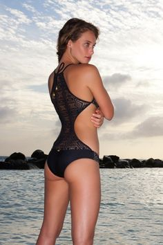 This one-piece looks like a bikini in the front with an unexpected crochet detail on the black. It ties at the neck for added support, Moderate coverage on the rear. Made in Columbia.