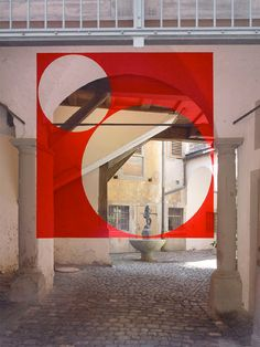 — Felice Varini - Anamorphosis.   Varini paints on architectural and urban spaces, such as buildings, walls and streets. The paintings are characterized by one vantage point from which the viewer can see the complete painting (usually a simple geometric shape such as circle, square, line), while from other view points the viewer will see 'broken' fragmented shapes.