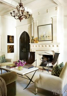 A contemporary banquette and a series of antique oils are smartly juxtaposed in the breakfast nook. The chrome-and-glass dining table is a vintage find, while the quatrefoil drum fixture is from Ainsworth-Noah. Painting, Huff Harrington Fine Art.