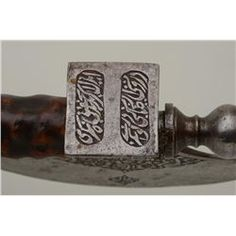 """Mid-Eastern battle axe with fancy etched, chased and engraved blade showing writing and figures of men smoking hookah and holding similar axes. This axe is mounted on an old knotted wood shaft which maybe it's original. The ax measures 29 ½ """" overall and the blade measures 8 ¼"""" across the width of the blade and 6 ¼"""" from edge to top."""