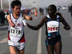 O alergătoare de maraton de top încetinește pentru a-l ajuta pe un bărbat cu dizabilități să-și deschidă sticla cu apă.