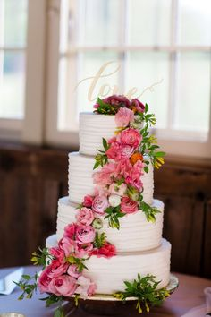 Four tier pink peony and ranunculus wrapped wedding cake: http://www.stylemepretty.com/pennsylvania-weddings/2017/02/21/a-little-pop-of-peony-takes-this-barn-to-another-level-of-beauty/ Photography: Asya Photography - http://asyaphotography.com/
