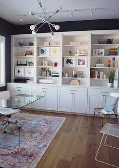 This home office is filled with colorful, abstract artwork. Dreamy, white built-in cabinets. A beautiful clear glass desk. Built In Shelves Living Room, Home Office Shelves, Office Built Ins, Home Office Cabinets, Basement Office, Built In Desk, Built In Bookcase, Home Office Organization, Home Office Space