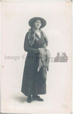FMP.85.20.13    ca. 1910  Macleod, AB    Young woman in full length dark suit wearing a fox fur stole and carrying a fox fur draped over her hands.