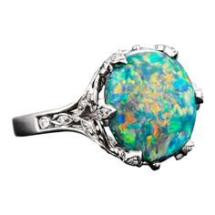 A majestic 5.54-carat black opal glistens with a litteral rainbow of color in this Tiffany & Co. ring. This highly-desirable gem is set in a fine foliate platinum mounting amongst .25 carats of diamond accents.