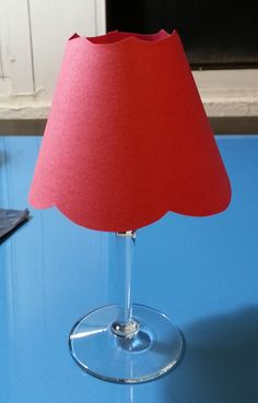 """Wineglasses make unique and pretty candle holders. They can be customized even further by adding a paper """"lamp shade"""". Here's how you can make your own unique wine glass lamps. Measure the distance across your wine glass opening at its..."""
