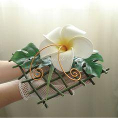 Original et épuré, ce porte alliance sera idéal pour un mariage au thème exotique. Réalisé sur un support quadrillé, ce coussin d'alliance est orné d'une fleur de frangipanier. Vous pourrez y maintenir vos alliances grâce aux deux arabesques orangées.