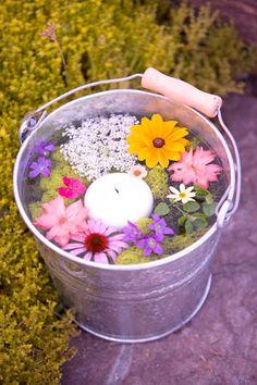Balde com flores e vela decorando e tornando a casa aconchegante