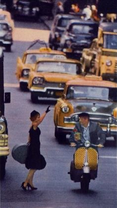 NYC, 1959. A very well dressed woman meets a very well dressed man riding a very colorful Vespa during Rush Hour. Sounds like the start of a romantic comedy to me.