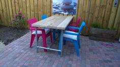 Stoere tuintafel gecombineerd met kleurige stoelen. Tafel van 5 cm dikke steigerplanken met een onderstel van stalen steigerbuis, op maat te bestellen bij Edwin Meijering klussen-meubels-interieur.