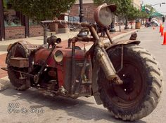Tractorbike. Hand made motorcycle with black iron pipe tubing for a frame. The main body sheet metal is from a Farmall Cub. International Harvester engine. 3 speed transmission out of a Crossly automobile, with reverse. Fenders are tire covers out of an old car covering David Bradley wheels. Sears town and country headlight. Model T tail light.