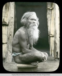 An Ainu man with long hair and beard sits cross legged on a wooden stool. He wears only a loin cloth, partially visible around his waist. In the backround of the image appears to be an entryway of a wooden dwelling. University of Oregon Libraries - Special Collections and University Archives Collection Title: Warner (Gertrude Bass) Lantern Slides