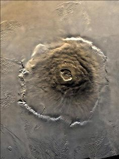 The biggest known volcano in the solar system is Olympus Mons on Mars, discovered by Mariner 9 in 1971. The mountain towers nearly 22 km (14 miles) above the surrounding plain, more than three times Mount Everest's elevation above sea level. It is more than 600 km across and occupies an area similar in size to Arizona. NASA/JPL.