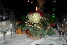 Centrotavola natalizio: piccolo cilindro in plastica con copertura di vera corteccia, rosa bianca al centro con nebbiolina e rami di abete, alloro e bacche rosse.