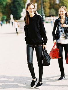 Black crew neck sweater, black leather pants, and black slip-on sneakers